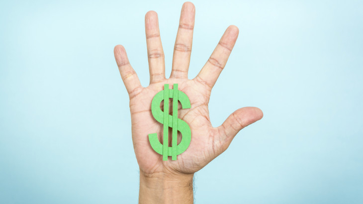 Hand up showing/catching a green dollar symbol with blue backgro